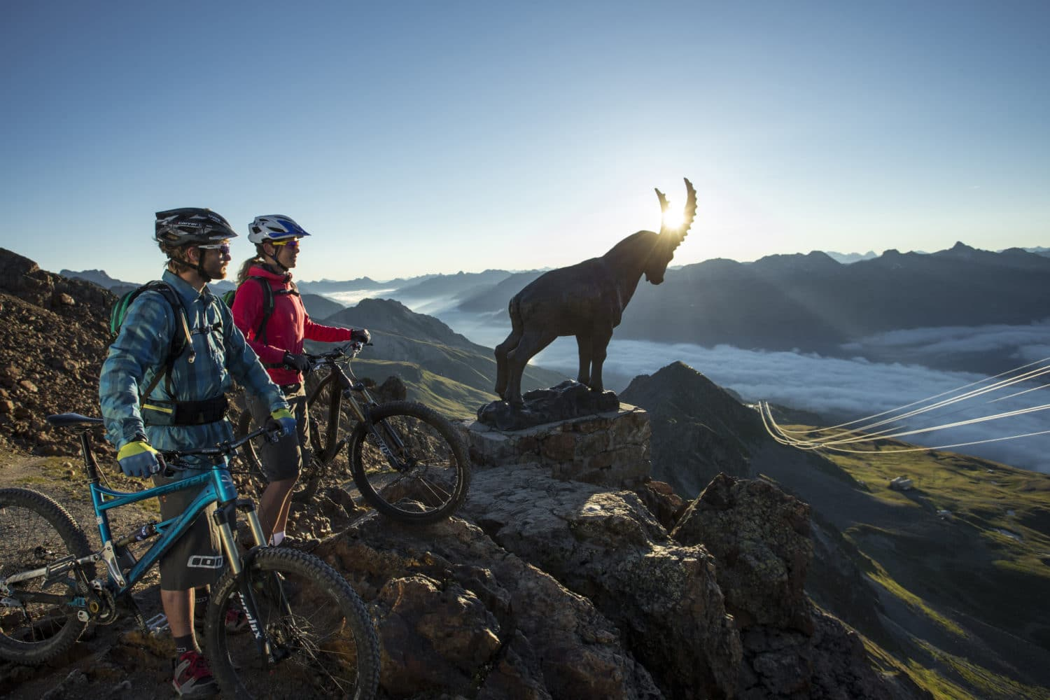 ENGADIN ST. MORITZ - Mountainbiker kurz nach Sonnenaufgang auf dem Piz Nair (3056m ue.M.) mit Steinbock. Mountain bikers shortly before sunrise on Piz Nair (3056 m), with ibex. Mountainbiker poco dopo il tramonto sul Piz Nair (3056m m s.l.m.) con stambecco. Copyright by: ENGADIN St. Moritz By-line: swiss-image.ch/Markus Greber