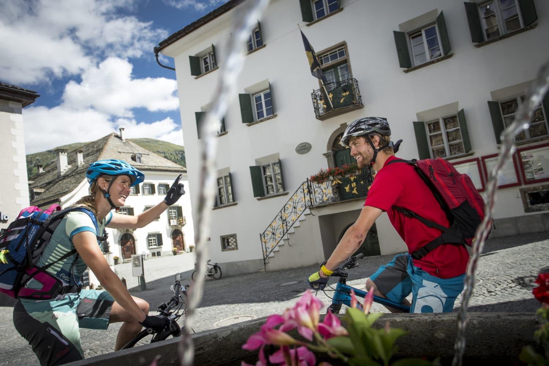 ENGADIN ST. MORITZ - Mountainbiker beim Brunnen im Dorfkern von Samedan. Im Hintergrund die Chesa Planta (links) und die Chesa Cumuenela (rechts).   Mountain bikers at the fountain in the centre of Samedan village.  Mountainbiker alla fontana in centro al paese di Samedan.  Sullo sfondo la Chesa Planta (a sinistra) e la Chesa Cumuenela (a destra).  Copyright by: ENGADIN St. Moritz By-line: swiss-image.ch/Markus Greber