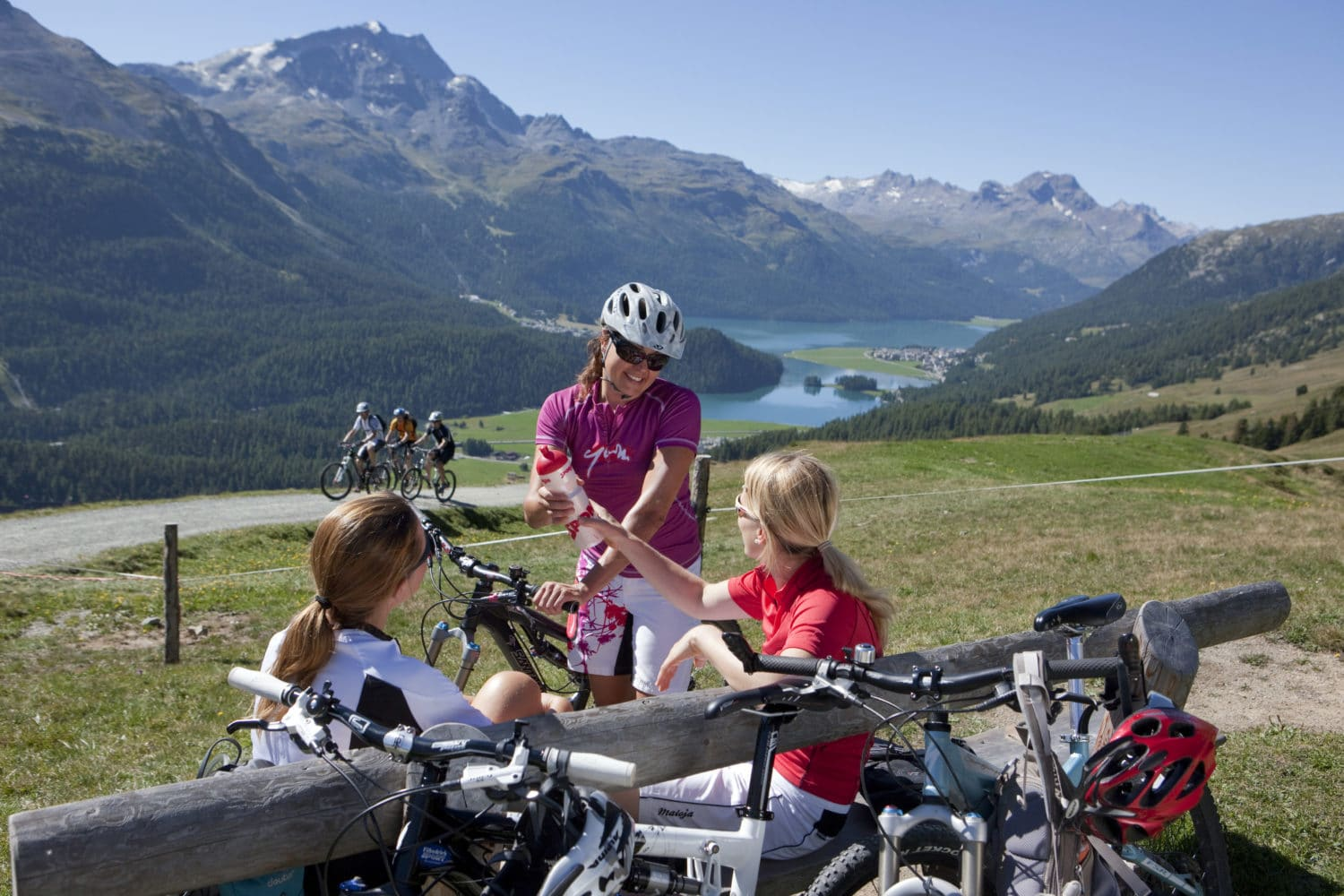 ENGADIN ST. MORITZ - Damengruppe mit Mountainbikes bei einer vitalisierenden Pause, im Hintergrund kommt eine Gruppe Maenner auf Mountainbikes, Engadiner Seen, Silvaplana, Piz Corvatsch (3451m) und Piz da la Margna (3159m). Group of women with mountain bikes taking a refreshing break. In background an approaching group of men on mountain bikes, Engadin lakes, Silvaplana, Piz Corvatsch (3,451m) and Piz da la Margna (3,159m). Gruppo di signore in mountainbike durante una pausa rivitalizzante. Sullo sfondo: gruppo di biker maschi in arrivo, laghi engadinesi, Silvaplana, Piz Corvatsch (3451m) e Piz da la Margna (3159m). Copyright by: ENGADIN St. Moritz By-line: swiss-image.ch/Christof Sonderegger