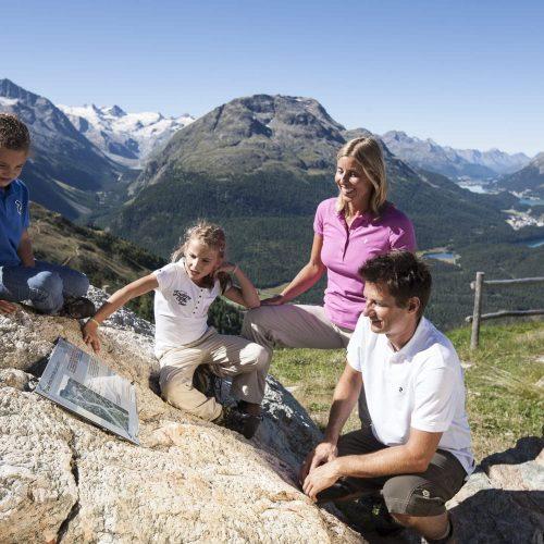 ENGADIN St. Moritz - Eine Familie bei einer Thementafel auf dem Klimaweg von Muottas Muragl zur Alp Languard. Im Hintergrund die Oberengadiner Seenlandschaft, die Sellagruppe und der Piz Rosatsch (3188m).  ENGADIN St. Moritz - family reading an information panel on the Climate Trail from Muottas Muragl to Alp Languard. In the background, the Upper Engadin lake landscape, Sella mountain range and Piz Rosatsch (3188m).  ENGADIN St. Moritz - Una famiglia davanti a una tavola tematica sul sentiero climatico da Muottas Muragl all'Alp Languard. Sullo sfondo il paesaggio dei laghi dell'Alta Engadina, il gruppo Sella e il Piz Rosatsch (3188m).  Copyright by: ENGADIN St. Moritz By-line: swiss-image.ch/Andrea Badrutt